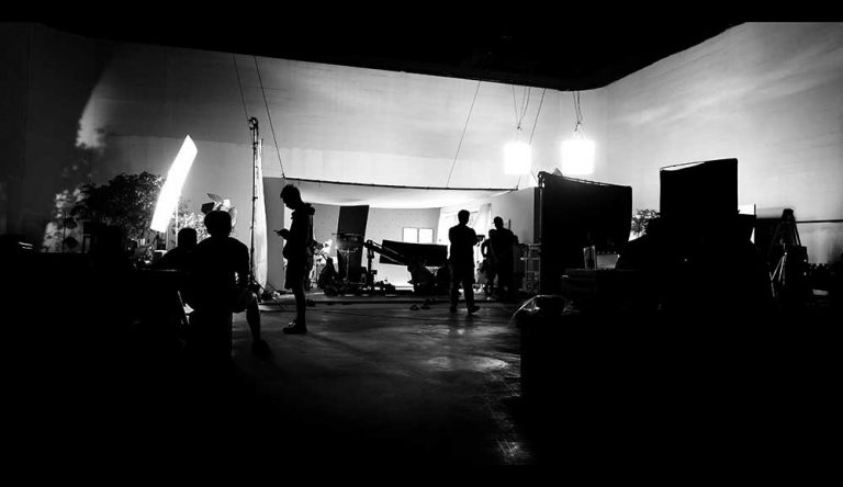 Video Outcomes corporate video production team at work on film set, lighting and production equipement in studio.